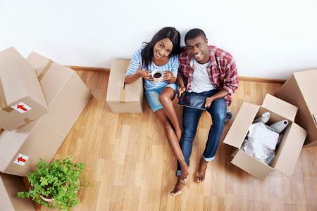 현대 태블릿 컴퓨터 기술을 사용하여 새 아파트에 상자를 이동하는 젊은 흑인 아프리카 부부의 오버 헤드보기