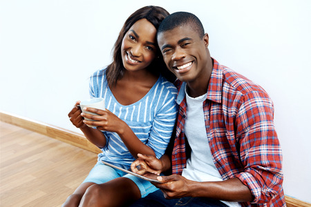 happy young african couple looking on tablet computer for new home furnishings for their apartment photo