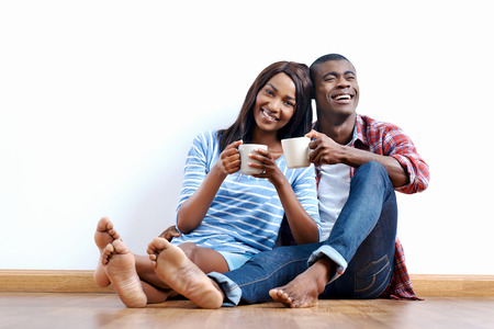 buying a house: Young african couple sitting on floor of new home with coffee and being happy with life success of property investment