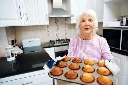 台所でマフィンのトレイを持って祖母