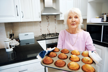 A grandmother holding a tray of muffins in the kitchen