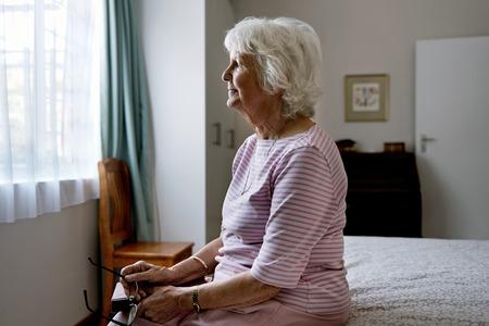 엄숙한 노인 여성 우울증을 다루는 그녀의 침대에 앉아