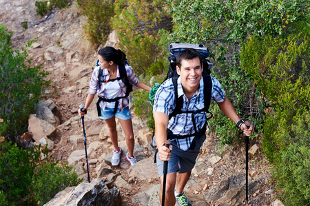 and hiking path: Smiling couple taking a break along the path of a hiking trail Stock Photo