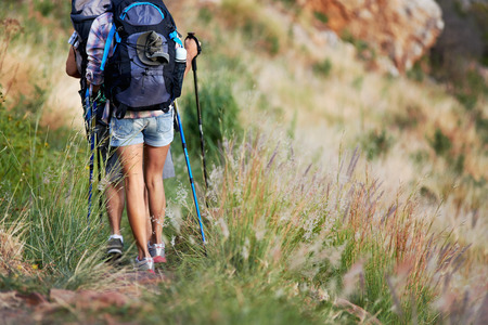 Cropped image of a backpacking couple walking along their hiking trail photo