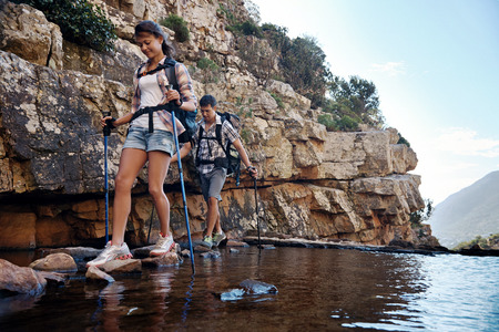 get across: An attractive hiking couple balancing on rocks to get across the water with copyspace