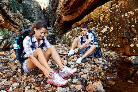 An active couple sitting down and taking a breather from their hike photo