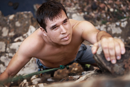 A good looking man with a face of concentration who is rock climbing photo