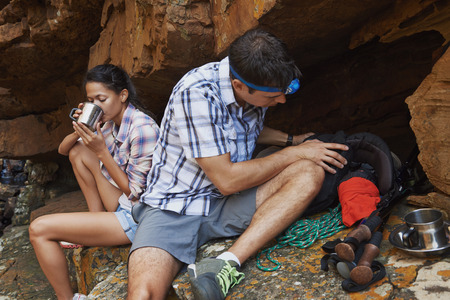 replenishing: A hiking couple taking a break by a cave with their hiking utensils around them Stock Photo