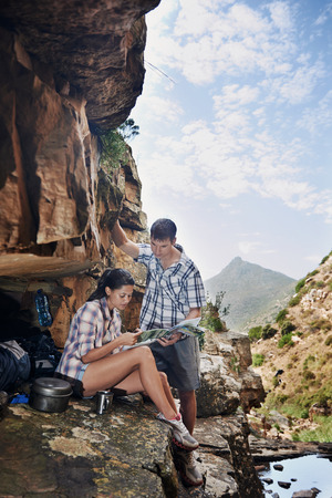 A couple taking a break from their hiking trail and looking at a map with copyspace photo