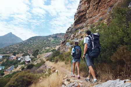 recreational climbing: A hiking couple walking along the trail of the bottom of the mountain with copyspace