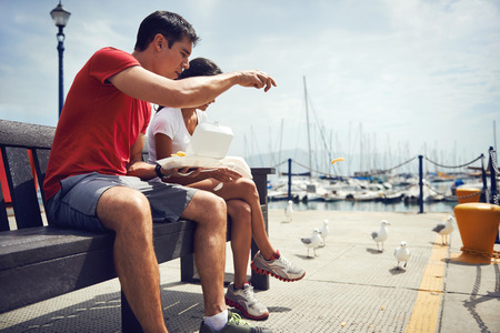 A young couple in fitness clothing eating take away fish and chips by the harbour with seagulls beside them photo