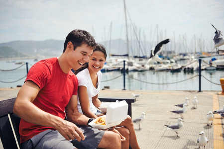 A relaxed and happy couple sitting together on a bench laughing together holding their takeaway fish and chips in a harbour photo