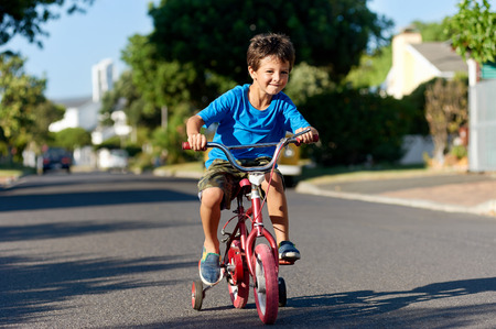 A young boy learning how to ride a bicycle on the street Stock Photo