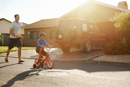 young boy learning to ride bicycle as father teaches him in the suburb street having fun. Stock Photo