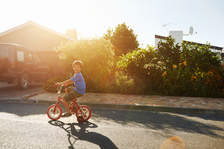 young boy learning to ride bicycle with training wheels at sunset