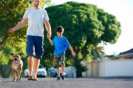 personas caminando: Un padre caminando con su perro y su hijo en los suburbios