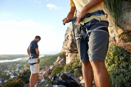Cropped image of two men putting on their harness and rock climbing equipment photo