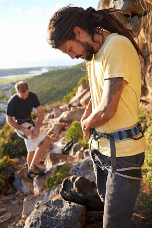 Two men putting on their harness and rock climbing equipment photo
