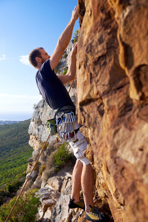 A man climbing a very steep mountain  -Rock Climbing photo