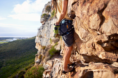 Men exercise: Cropped image of a man with rock climbing equipment climbing up a steep mountain Kho ảnh