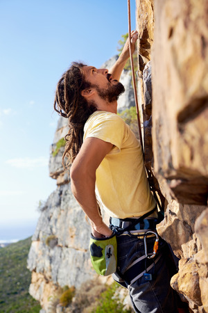rock climb: A man with dreadlocks climbing up a steep mountain with a harness and rope and looking up Stock Photo
