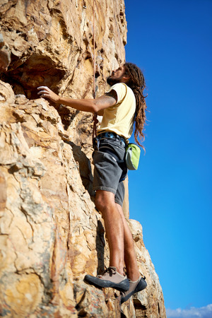 rockclimber: Rockclimber with dreadlocks climbing a mountain Stock Photo
