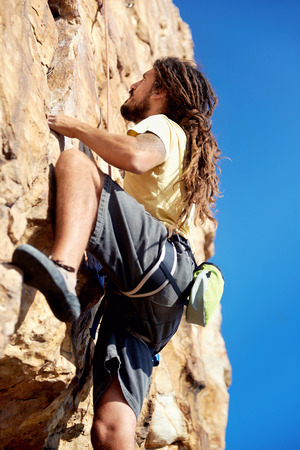 extreme angle: A rockclimber finding a foothold on the steep mountain hes climbing