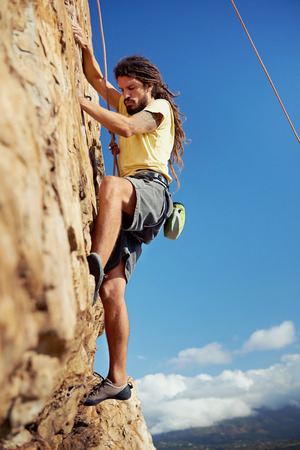 A rockclimber finding a foothold on the steep mountain hes climbing