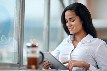 커피와 함께 사무실에서 일을 태블릿 컴퓨터를 사용하는 젊은 비즈니스 여자 투자 스톡 콘텐츠