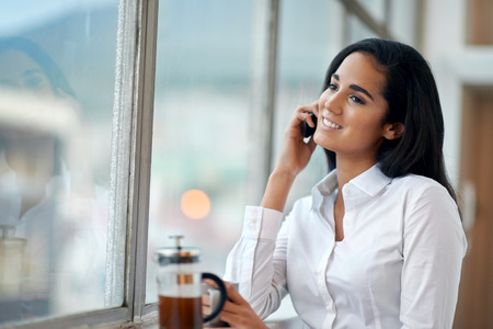 Happy businesswoman on work call with coffee and window smiling photo