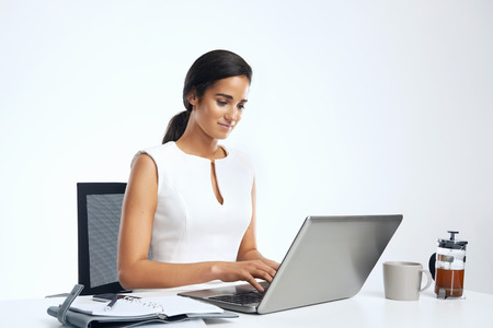 woman typing: woman working at desk with laptop and coffee in business