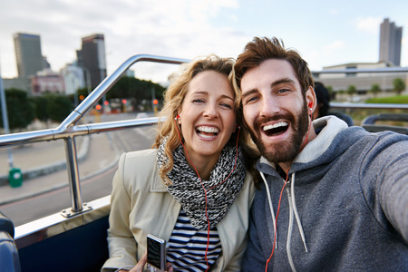 dating: tourist couple travel selfie on open top tour bus in city Stock Photo