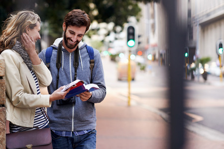 summer vacation: travel couple walking around city on vacation with guide book having fun