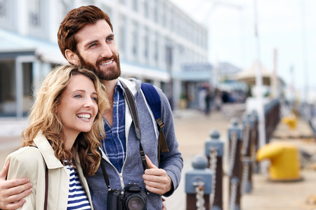 portrait of cheerful affectionate tourist couple with camera on vacation photo
