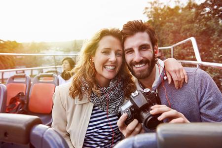 休日休暇観光バスを楽しんでいるカップルの肖像画オープン トップ ツアー