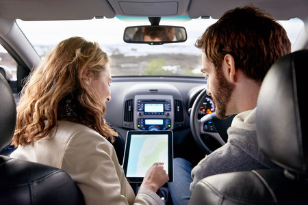 car navigation: couple using gps on tablet compter to navigate in car on holiday