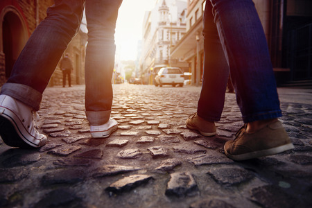 tours: tourist couple walking on cobblestone street vacation in europe on holiday break