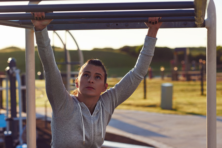 pull up: young athletic fitness woman working out at outdoor gym doing pull ups at sunrise