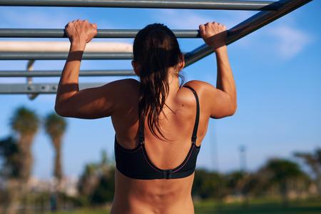 Mladá atletický fitness žena pracuje se na venkovní tělocvičně vede pull up při východu slunce