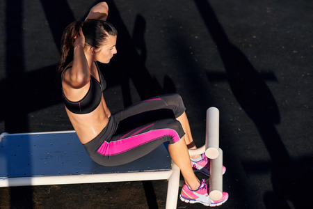 situp: fitness woman doing situps in outdoor gym woking out strength training