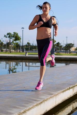 atleta corriendo: fitness mujer activa en parque con auriculares para música mientras corre Foto de archivo