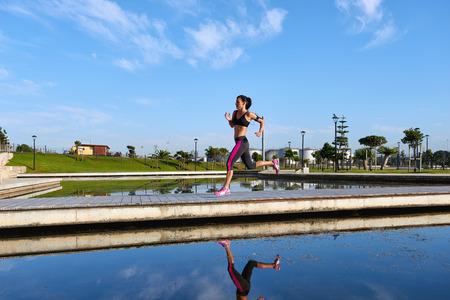 stride: woman running over bridge with fitness marathon training stride