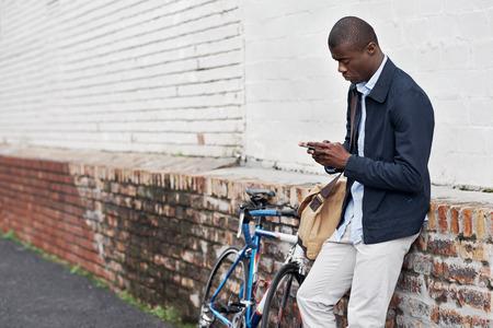 modelos negras: Hombre inconformista con la bicicleta que envía el mensaje en el teléfono celular móvil en la ciudad urbana