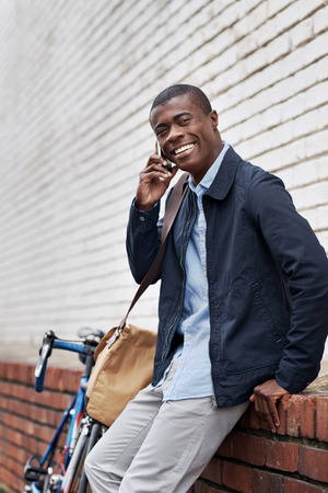 happy young black african man with cell phone having conversation on mobile photo