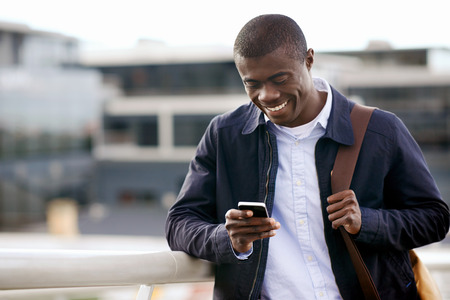 šťastný mladý černý africký muž s mobilním telefonem, který má konverzace na mobil
