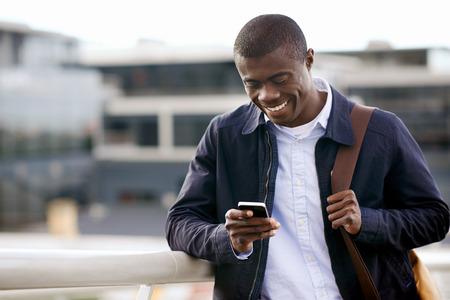 africanas: feliz joven hombre negro africano con el teléfono celular que tiene una conversación en el móvil Foto de archivo
