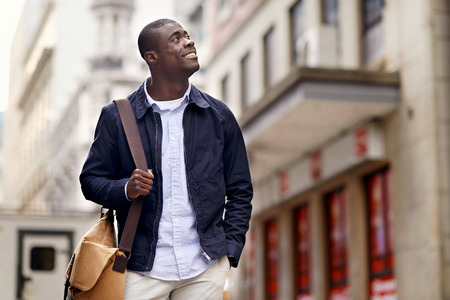 happy young man: Friendly young trendy african black man walking around the urban city having fun