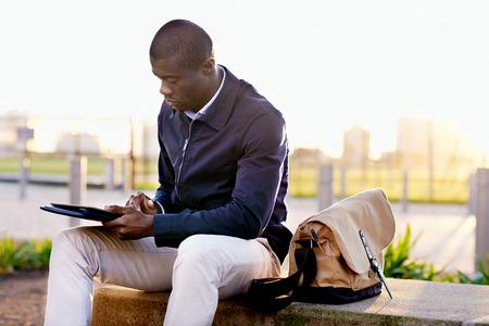 仕事の合間に公園でタブレット コンピューターを使用してアフリカの黒いビジネス男ヒップスター