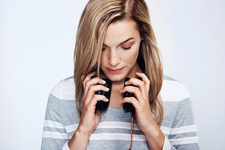 audifonos dj: Retrato de mujer joven escuchando m�sica en los auriculares dj Foto de archivo