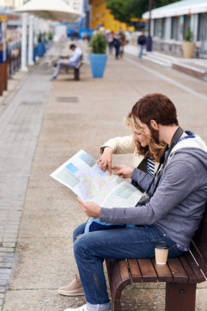 lost city: tourist couple sitting on bench looking at map Stock Photo